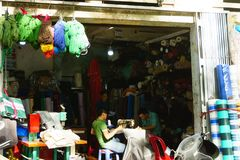 胡志明,越南- 2017年11月20日:许多年轻人与在街道的缝纫机一起使用 免版税图库摄影