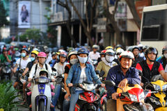 胡志明,越南- 2014年10月29日:人们去工作在摩托车旁边 免版税图库摄影