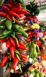 胡椒、垂悬在市场上的大蒜和花 库存图片