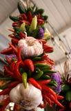 胡椒、垂悬在市场上的大蒜和花 免版税库存图片