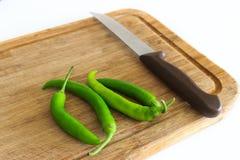 胡椒和刀子在砧板 库存图片