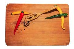胡椒和大蒜以绿色在织地不很细木板有copyspace的 免版税库存照片
