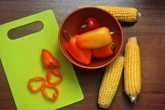 胡椒和玉米在一个木板 库存图片