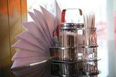 胡椒和盐瓶、牙签和餐巾在桌上在咖啡馆在窗口前面在晚上 图库摄影