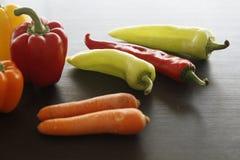 胡椒和红萝卜在木桌上 免版税库存图片