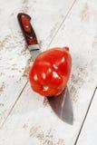 胡椒蕃茄用在白色木头的刀子切开了 免版税库存图片