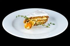 胡萝卜糕开胃片断在一块白色板材的在黑暗的backgro 免版税库存照片