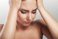 胳膊关心健康查出滞后 图片是遭受可怕的严厉头疼的一个美丽的少妇接触她的面孔 疲劳,被耗尽 免版税图库摄影