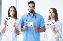 胳膊关心健康查出滞后 拿着帮助的医疗队题字在H 免版税库存图片
