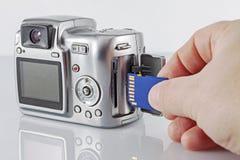 胳膊在照相机插入USB闪光驱动 免版税图库摄影
