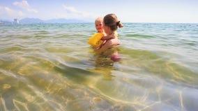 胳膊小女儿的白肤金发的母亲举行在天蓝色的海 股票视频