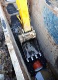 胳膊挖掘机的开掘的管道污水 免版税库存图片