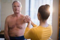 给胳膊的女性治疗师背面图按摩资深男性患者 库存图片