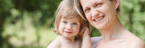 胳膊的愉快的矮小的微笑的孩子  免版税库存照片