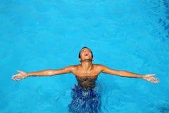 胳膊穿蓝衣的男孩开放池放松了少年&# 图库摄影