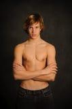 胳膊被折叠的男性青少年的腰部 库存图片