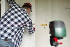 胶合在家贴墙纸 年轻人,工作者投入墙纸在墙壁 家庭整修概念 免版税库存照片