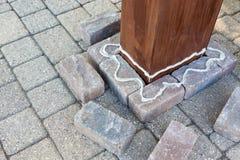 胶合应用对砖在一根木柱子附近 免版税库存图片