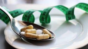 胶囊和药片在板材有叉子、饮食和减重的,磁带 库存图片