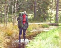 胶靴的年轻,大力士走通过沼泽的在前面 免版税库存照片