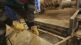 胶靴的民工倾斜在挖泥机机器的岩石 影视素材