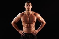 胸部赤裸的男性身体建造者用在臀部的手 免版税库存图片