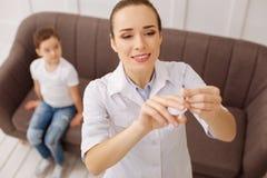 能干的儿科医生小心以疫苗比例 免版税库存照片