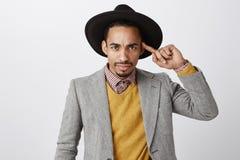 能您在行动前认为 生气的愤怒的年轻商人画象与胡子的在黑帽会议和夹克 免版税图库摄影
