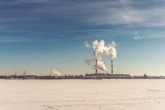 能源厂,能量在冻河的发电站蓝天的区域或湖 免版税库存图片