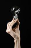 能源消耗和节能题目:拿着在黑背景的人的手一个电灯泡在演播室 库存照片