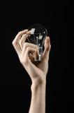 能源消耗和节能题目:拿着在黑背景的人的手一个电灯泡在演播室 免版税库存图片