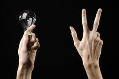 能源消耗和节能题目:拿着在黑背景的人的手一个电灯泡在演播室 库存图片