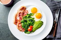 能转化为酮的饮食早餐煎蛋、烟肉和鲕梨、菠菜和防弹咖啡 低碳高脂肪早餐 免版税库存照片