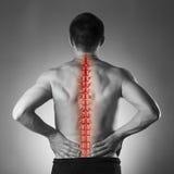 脊椎痛苦、人以腰疼和疼痛在脖子,黑白照片与红色中坚 库存图片
