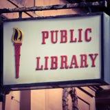 脏和被风化的公立图书馆标志 库存图片