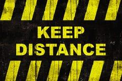 脏的`保留与黄色和黑条纹的距离`文本警报信号 库存图片