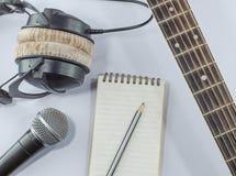 脖子在顶视图的吉他笔记本与音乐概念whitebackground 免版税图库摄影