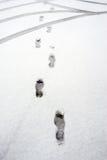 脚印和轮胎在雪 库存图片