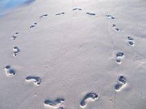脚印圈子在海滩沙子的 库存图片