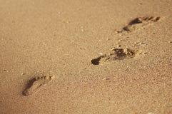 脚印或踪影在夏天沙子海滩或海岸线在度假-背景纹理-顶视图 库存照片