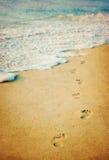 脚印的Grunge图象在一个热带海滩的 图库摄影