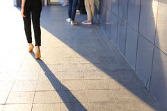 脚在商业中心的背景前进的女孩 库存照片