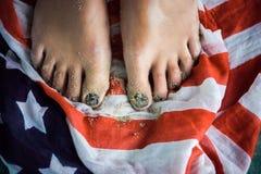 脚女孩在美国的旗子站立 绿色委员会 免版税库存照片