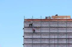 脚手架的工作者修建从块和砖的九层房子 图库摄影