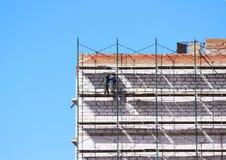 脚手架的工作者修建从块和砖的九层房子 库存图片