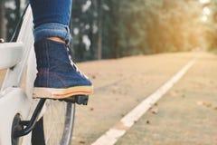 脚有白色自行车的妇女在自然背景中 免版税图库摄影