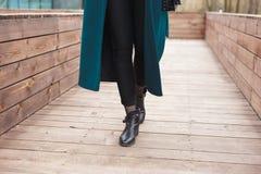 黑脚腕起动、黑皮包、温暖的鲜绿色外套和黑长裤 步行的时髦和时兴的女孩 免版税图库摄影