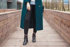 黑脚腕起动、黑皮包、温暖的鲜绿色外套和黑长裤 步行的时髦和时兴的女孩 库存图片