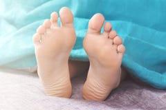 脚被子在床上的早晨醒从长沙发起来 库存照片