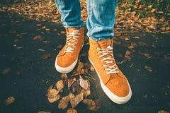 脚走在秋天的运动鞋留给室外 库存照片